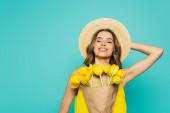 Veselá žena v klobouku drží tulipány izolované na modré