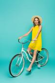 Stylová žena v letních šatech na kole na modrém pozadí