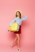 Csinos utazó napszemüveg tartó bőrönd és séta rózsaszín háttér