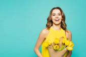 Veselá žena drží žluté tulipány izolované na modré
