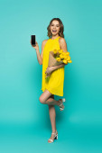 Veselá žena ukazuje mobilní telefon a drží tulipány na modrém pozadí