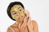 soustředěná mladá žena nanášení zelené masky na obličej s rukama na bílém pozadí