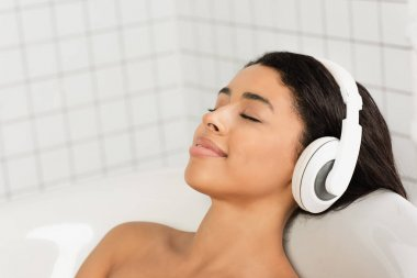 Smiling young woman with closed eyes resting and listening music in headphones in bathroom stock vector