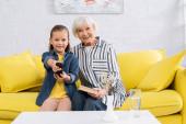 Lächelnde Großmutter und Kind vor dem Fernseher auf der Couch