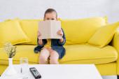 Lány könyv közel arc kanapén otthon