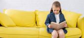 Dívka čtení knihy na žlutém gauči, prapor