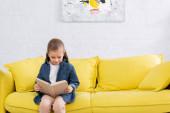 Dítě v neformálním oblečení čtení knihy doma