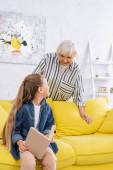 Dítě s knihou při pohledu na pozitivní babičku v obývacím pokoji