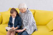 Nagyi és a gyerek könyvet olvas a sárga kanapén