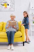 Starší žena čte knihu blízko usmívající se dítě doma