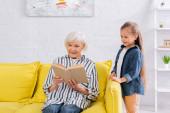 Nagymama könyvet olvas közel boldog lány otthon