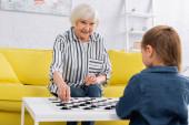 Ältere Frau lächelt beim Schachspiel mit verschwommenem Kind