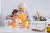 Oma und Kind kochen gemeinsam in der Küche
