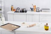 Tészta, keksz vágó és sodrófa az asztalon liszt közelében a konyhában