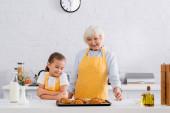 Veselá babička a dítě při pohledu na chutné croissanty na kuchyňském stole