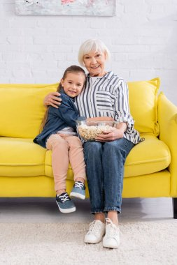 Child smiling at camera while hugging granny with popcorn on couch stock vector