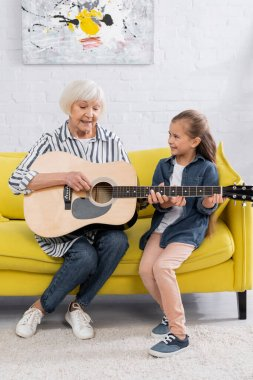 Cheerful grandmother and kid playing acoustic guitar on couch