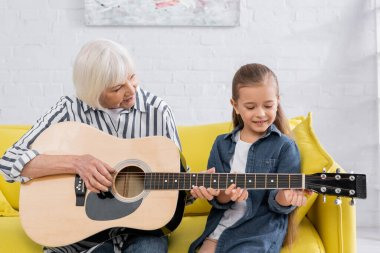Happy kid playing acoustic guitar with granny in living room