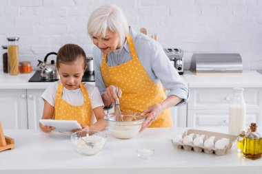 Kid using digital tablet near granny cooking in kitchen stock vector