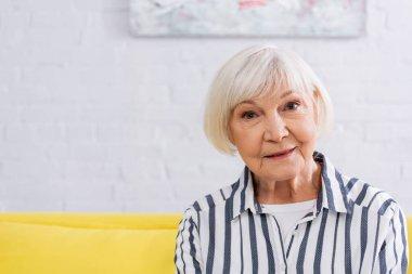 Senior woman looking at camera at home stock vector