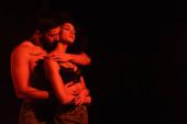 Muž bez košile objímající africké americké přítelkyně izolované na černošky s červeným osvětlením