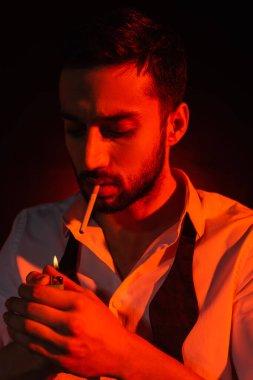Siyah arka planda kırmızı ışıkta çakmak tutan sakallı adam.