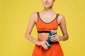 oříznutý pohled na ženu v oranžovém sportovním oblečení drží sportovní láhev izolované na žluté