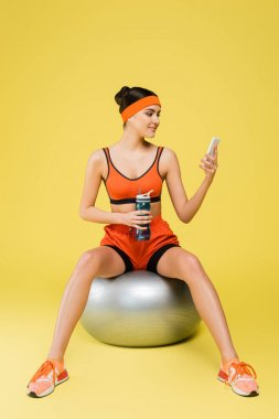Woman in sportswear sitting on fitness ball with sports bottle and looking at smartphone on yellow background stock vector