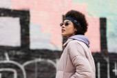 Mladá africká americká žena v šátek a sluneční brýle stojící na městské ulici
