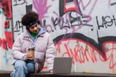 Africká americká žena drží kávu jít a pomocí notebooku v blízkosti graffiti venku