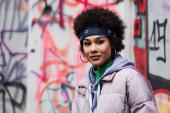 Afričanky americká žena při pohledu na kameru v blízkosti rozmazané graffiti venku