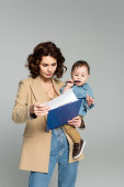 curly businesswoman in blazer holding clipboard and baby boy in arms isolated on grey
