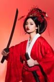 Japanerin in orientalischer Kleidung mit Scheide und Schwert auf rotem Hintergrund