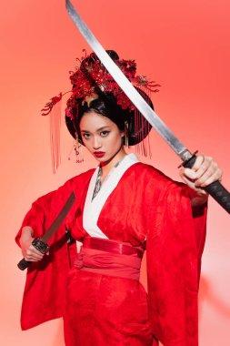 Japon kadın kırmızı arka planda kılıç tutuyor.