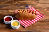 köstliche Würstchen mit kleiner US-Flagge in der Nähe von Schüsseln mit Ketchup und Senf auf Holztisch