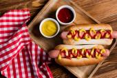 pohled shora na hot dogy, kečup a hořčici v blízkosti kostkovaného ubrousku na dřevěném stole