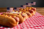 leckere Hot Dogs mit Soßen und kleinen amerikanischen Flaggen auf karierter Tischserviette isoliert auf grau