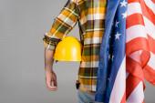 Rückseite des beschnittenen Arbeiters mit Hut und US-Fahne isoliert auf grau, Labor Day Konzept