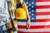 abgeschnittene Ansicht des Arbeiters in kariertem Hemd und Werkzeuggürtel hält Hardhat in der Nähe verschwommene US-Flagge, Labor Day Konzept
