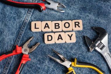 İşçi Bayramı yazılı küplerin üst görünümü kot kumaş üzerinde çeşitli araçların yanında