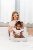 happy mother tying hair of adopted african american kid watching movie on laptop in bedroom