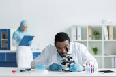 African american scientist in white coat looking through microscope near test tubes and digital tablet