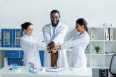 Smiling interracial scientists holding hands near test tubes and clipboard in laboratory