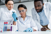 African american scientists standing near colleague with pipette and test tubes