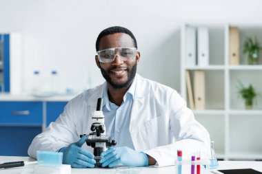 Koruyucu gözlüklü gülümseyen Afrikalı Amerikalı bilim adamı laboratuvarda mikroskobun yanındaki kameraya bakıyor.