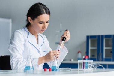 Bilim adamı laboratuardaki elektronik pipetten kan örneği alıyor.