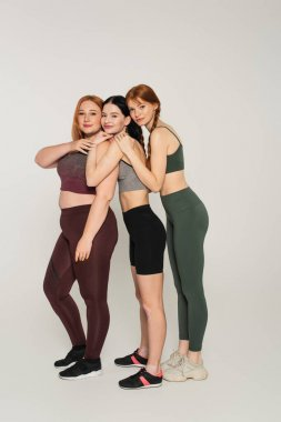 Full length of smiling body positive women in sportswear embracing each other on grey background