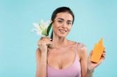 veselá žena s opalovacím krémem a bílá lilie při pohledu na kameru izolované na modré