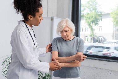 African american traumatologist standing near senior woman touching arm