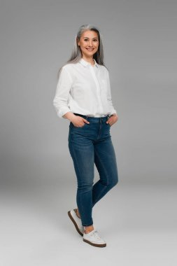 full length view of middle aged woman with hands in pockets of blue jeans smiling on grey